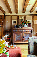 Interior of an English cottage with period furniture and floral display in a confortable lounge with exposed ceiling timbers.