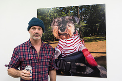 """© Licensed to London News Pictures. 28/03/2018. LONDON, UK.  Glaswegian street photographer Dougie Wallace stands in front of one his images from his new book """"Well Heeled"""", a book about dogs.  Preview of """"The Series"""", an exhibition by Dougie Wallace at Bermondsey Project Space from 27 March to 14 April.  Works on display are from diverse subjects such as the mega-rich in Harrodsburg, Shoreditch, Blackpool as well as his latest project """"Well Heeled"""", a street photography book with dogs as the subject.  Photo credit: Stephen Chung/LNP"""