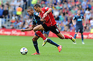 Cardiff city's Peter Odemwingie goes past Newcastle's Loic Remy. Barclays Premier League match, Cardiff city v Newcastle Utd  at the Cardiff city stadium in Cardiff, South Wales on Saturday 5th Oct 2013. pic by Andrew Orchard, Andrew Orchard sports photography,