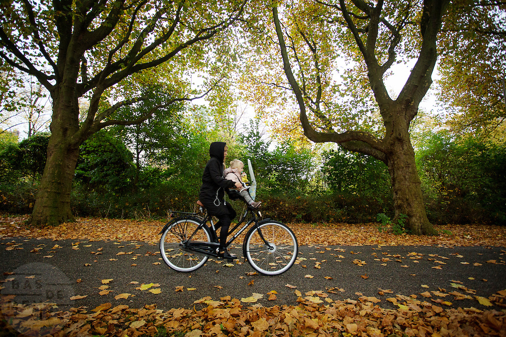 In Delft rijden fietsers door een herfstbui.<br /> <br /> In Delft cyclists ride at a rainy day at autumn.
