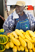 Stallholder at vegetable stall in French Market food market on Decatur Street, French Quarter of New Orleans, USA