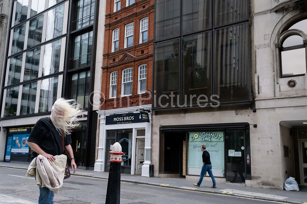As the Met Office issued alerts for very strong winds across southern England and Wales, a weather system named Storm Francis, a middle-aged mans white hair blows forward to partially obscure his eyesight while walking along Fenchurch Street in the City of London, the capitals financial district, on 25th August 2020, in London, England.