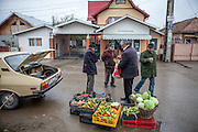 Roma activist Gheorghe Tudor shopping vegetables during the Saturday morning market place located at the main road in Marginenii de Jos.