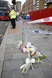 © Licensed to London News Pictures. 06/07/2021. London, UK. Floral tributes are placed at a crime scene on Woolwich New Road in south east London after a 15 year old boy was stabbed to death. Officers were called at 17:23hrs on Monday, 5 July to reports of a stabbing on Woolwich New Road, SE18. Police found a 15-year-old boy suffering from a stab injury. They immediately provided first aid prior to the arrival of the London Ambulance Service. Despite their efforts, he was pronounced dead at the scene. Photo credit: Peter Macdiarmid/LNP