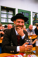 Man drinking beer at the Augustinerbrau Festhalle (Festival Hall) beer tent, Oktoberfest, Munich, Bavaria, Germany.