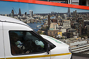 A van driver parked by a construction hoarding showing grand aerial views from the top of One Blackfriars on the Southbank, on 8th May 2017, in London, England.