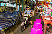 27 APRIL 2013 - BANGKOK, THAILAND:   A woman rides a motorscooter through a market in Talat Noi. The Talat Noi neighborhood in Bangkok started as a blacksmith's quarter. As cars and buses replaced horse and buggy, the blacksmiths became mechanics and now the area is lined with car mechanics' shops. It is one the last neighborhoods in Bangkok that still has some original shophouses and pre World War II architecture. It is also home to a  Teo Chew Chinese emigrant community.         PHOTO BY JACK KURTZ