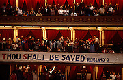With a banner telling them they shall be saved from evil, Christians worship together in the Royal Albert Hall