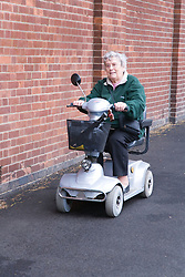 Older woman riding an electric mobility scooter down the road,