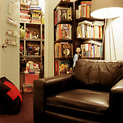A very large looking black leather chair with a modern floor lamp with a round light colored shade directly behind it. There is a large bookcase full of books and some dolls behind the chair, some titles being for children and young adults. There is an open door in the left background, a closet with more toys and dolls, and a large black pillow with a red + sign, like the Swiss flag,  leaning against the door.