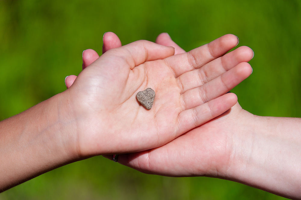 A mother and a daughter holding a heart-shaped rock found on a trail in Glacier National Park