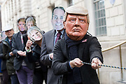 Protesters from War on Want stage a demonstration outside the governments Department for International Trade building in London, England, United Kingdom, on 6th February 2018, calling on Members of Parliament MPs to demand the parliamentary scrutiny of trade deals. The protestors are wearing costumes depicting Donald Trump, Theresa May and Liam Fox.