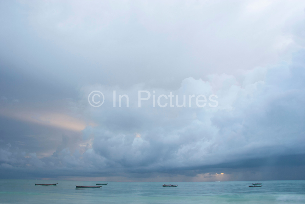 Fishing boats float in the Indian ocean, just off the coast at Paje on 2nd December 2008 in Zanzibar, Tanzania. The calm seas at sunrise with billowing clouds tinged with changing colours is breathtaking. The quietest, most peaceful part of the day. Zanzibar is a small island just off the coast of the Tanzanian mainland in the Indian Ocean. In part due to its name, Zanzibar is a travel destination of mystical reputation, known for its incredible sealife on its many reefs, the powder white coral sand beaches and the traditional cultivation of spices.