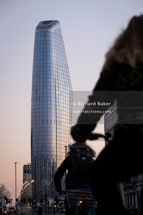 Seen from the City of London, One Blackfriars (one of the capital's newest skyscrapers) rises above cyclists in evening rush-hour traffic, on 27th February 2021, in London, England. Located on Bankside, the south bank of the river Thames, the development is a 52-storey 170m tower whose uses include residential flats, a hotel and retail.