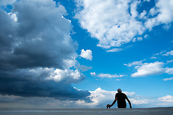 © Licensed to London News Pictures. <br /> 10/06/2014. <br /> <br /> Saltburn, United Kingdom.<br /> <br /> A man sits on a wall looking on as dark thunder clouds form over Teesside.<br /> <br /> Photo credit : Ian Forsyth/LNP