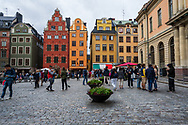 Stockholm, Sweden -- July 16, 2019. Crowds of tourists in Old Town, Stockholm, explore a town square with colorful buildings.
