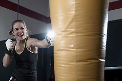 Sportswoman doing strength training by punching on punch bag in the gym, Bavaria, Germany