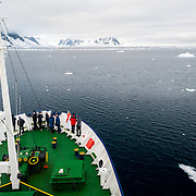 """Passengers stand out on the bow of a cruise ship to admire the view when passing through the Lemaire Channel, sometimes known as """"Kodak Gap"""" for its scenic views."""
