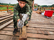 16 SEPTEMBER 2014 - SANGKHLA BURI, KANCHANABURI, THAILAND: A soldier in the Thai army pulls nail out of a piece recycled lumber while he works on the repair of the Mon Bridge. The 2800 foot long (850 meters) Saphan Mon (Mon Bridge) spans the Song Kalia River. It is reportedly second longest wooden bridge in the world. The bridge was severely damaged during heavy rainfall in July 2013 when its 230 foot middle section  (70 meters) collapsed during flooding. Officially known as Uttamanusorn Bridge, the bridge has been used by people in Sangkhla Buri (also known as Sangkhlaburi) for 20 years. The bridge was was conceived by Luang Pho Uttama, the late abbot of of Wat Wang Wiwekaram, and was built by hand by Mon refugees from Myanmar (then Burma). The wooden bridge is one of the leading tourist attractions in Kanchanaburi province. The loss of the bridge has hurt the economy of the Mon community opposite Sangkhla Buri. The repair has taken far longer than expected. Thai Prime Minister General Prayuth Chan-ocha ordered an engineer unit of the Royal Thai Army to help the local Mon population repair the bridge. Local people said they hope the bridge is repaired by the end November, which is when the tourist season starts.    PHOTO BY JACK KURTZ