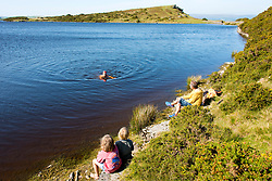 © Licensed to London News Pictures. 18/09/2020.  Builth Wells, Powys, Wales, UK. As the heatwave continues in Wales a family go wild swimming in a lake on the Mynydd Epynt moorlad near Builth Wells in Powys, UK. Photo credit: Graham M. Lawrence/LNP