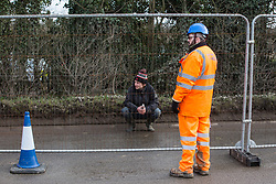 Harefield, UK. 8 February, 2020. An environmental activist crouches behind Heras-style fencing erected by HS2 engineers on Harvil Road in the Colne Valley in preparation for tree felling work for the high-speed rail link. Environmental activists based at a series of wildlife protection camps in the area used a variety of tactics to prevent the tree felling work, for which road and rail closures had been implemented, for the duration of the weekend for which it had been scheduled.