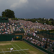Clouds gather ominously as the hill at Wimbledon is packed to watch Andy Murray the Great British hope in action against Viktor Troicki of Serbia on the big screen. Meanwile on court 18, Igor Andreev of Russia dives in despair as he and his mixed doubles partner  Maria Kirilenko take on Andy Ram and Anna Chakvetadze at the All England Lawn Tennis Championships at Wimbledon, London, England on Saturday, June 27, 2009. Photo Tim Clayton.
