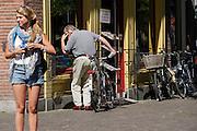In Utrecht kijkt een man in de etalage van boekwinkel Bijleveldt aan de Janskerkhof. Op de voorgrond wacht een meisje met een korte spijkerbroek op haar afspraak.<br /> <br /> In Utrecht a man is looking in the shopping window of a bookshop. A young girl with short trousers is waiting for her appointment.