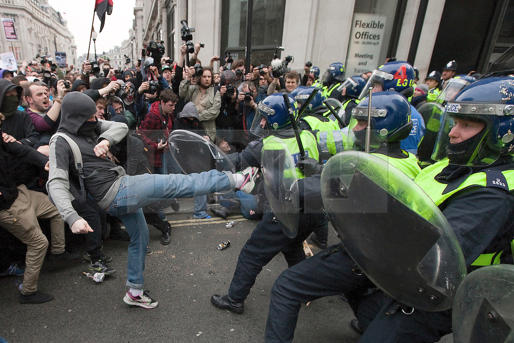 """© under license to London News Pictures. 25/03/2011: Masked protesters fight with police in riot gear on Regent Street during a day of protests. One protester kicks out at the police line. Credit should read """"Joel Goodman/London News Pictures""""."""
