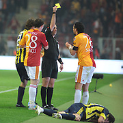 Referee's Firat AYDINUS (C) show the yellow card to Galatasaray's Servet CETIN (R) during their Turkish superleague soccer derby match Galatasaray between Fenerbahce at the Turk Telekom Arena in Istanbul Turkey on Friday, 18 March 2011. Photo by TURKPIX