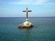 The Sunken Cemetery of Camiguin Island<br /> <br /> Camiguin is an island province of the Philippines located in the Bohol Sea, about 10 kilometers off the northern coast of Mindanao. The island of Camiguin is of volcanic origin and composed of four young stratovolcanoes overlying older volcanic structures. These include Mt. Vulcan and Mount Hibok-Hibok, still considered active having last erupted in 1953.<br /> <br /> During the volcanic eruption of Mt. Vulcan that lasted from 1871 to about 1875, after continuously spewing out lava into the sea, it gained a height of nearly 2,000 feet and submerged areas of Catarman, including the town's cemetery. Today, all that remains of old Catarman are the ruins of an ancient Spanish San Roque church, a convent and a bell tower. Remnants of the structures and gravestones of the cemetery were still seen during low tide until 1948 when Mount Vulcan erupted for the fourth time, which buried the area deeper by 20 feet. In 1982, a large cross was built on the solidified lava to mark this old gravesite. <br /> ©Amazing Planet/Exclusivepix