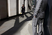 As a woman walks past, an anonymous man wearing shiny grey suit stands in narrow sunlit lane in the City of London. With a hand in a pocket, the anonymous man smokes a cigarette during a break in his working day. It is mid-afternoon and the male enjoys warm spring sunshine in this narrow pedestrian lane He is a grey man in grey clothing, suitably merging with monochrome architecture and landscape.
