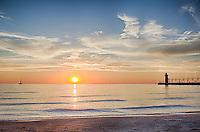 A sailboat on the horizon set sail sail towards the setting sun on Lake Michigan