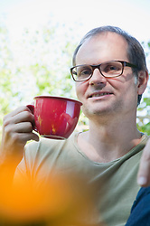Mature man with cup of coffee, smiling, portrait