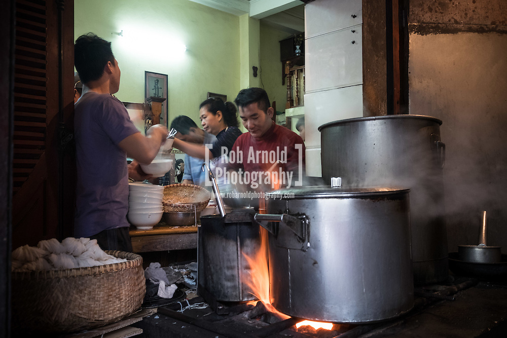 Staff preparing bowls of Pho Bo (beef noodle soup) at the iconic Pho Gia Truyen at 49 Bat Dan in Hanoi's Old Quarter.