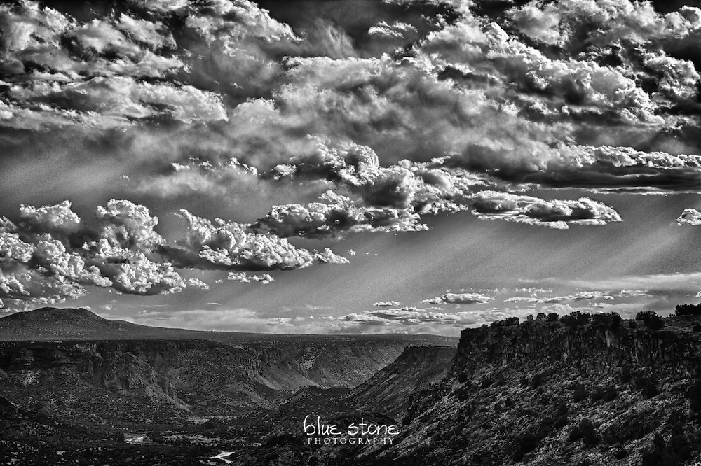Black and white photograph of mountains in the distance with the sunlight piercing through the storm clouds as the sun sets.<br /> <br /> Wall art is available in metal, canvas, float wrap and standout. Art prints are available in lustre, glossy, matte and metallic finishes.