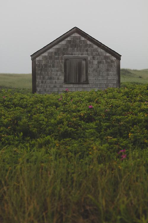 A rugged beach hut on the sandy bluffs of Nantucket's southern coast.