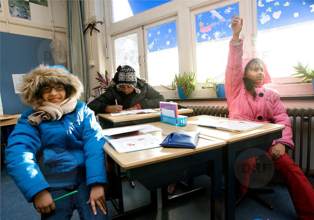 Nederland Rotterdam 15 februari 2008 20080215.Warme Truiendag. Kinderen van basisschool Odilia gehuld in dikke truien in klaslokaal om energie te besparen en de co2 uitstoot te verminderen. De Warme Truiendag is elk jaar op of rond 16 februari, de dag waarop in 2005 het Kyoto-protocol in werking trad. In 2008 is gekozen voor de werkdag die het dichtst bij deze datum ligt: vrijdag 15 februari. De bedoeling van het Kyoto protocol is om de uitstoot van broeikasgassen, die leiden tot klimaatverandering, wereldwijd te verminderen..De dag herinnert iedereen aan de afspraken van het verdrag: ook in Nederland moet de uitstoot van broeikasgassen verminderen.??Het Klimaatverbond roept samen met Z@APP op Nederland 3, iedereen in Nederland op om vrijdag 15 februari 2008 mee te doen aan de Warme Truiendag. Ga die dag in een warme trui naar school of kantoor en vraag de directie de verwarming enkele graden lager te zetten. De verwarming één graad lager betekent 7% minder energieverbruik en dus 7% minder CO2-uitstoot. Hiermee kun je het klimaat sparen zonder comfortverlies. Lees op www.warmetruiendag.nl meer over hoe je deze dag op school en op kantoor nog meer kunt aankleden en invulling geven..Minder CO2-uitstoot door Warme Truiendag ..Vrijdag 15 februari is het Warme Truiendag. Op deze dag komen leerlingen en leerkrachten van deelnemende scholen in een warme trui naar school. Hierdoor kan de verwarming enkele graden naar beneden. Eén graad lager betekent al 7% minder energieverbruik en dus 7% minder CO2-uitstoot...De Warme Truiendag vindt jaarlijks plaats rond 16 februari omdat op deze dag in 2005 het Kyotoprotocol werd ondertekend. De Warme Truiendag herinnert iedereen aan de afspraken van het verdrag. De gemeente Rotterdam vindt de Warme Truiendag een goede manier om het klimaatbeleid onder de aandacht te brengen. De stad neemt de actie over in het kader van het Rotterdam Climate Initiative. Het is een concrete vorm om kinderen en ouders te informeren over energiebesparing en