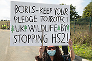 An anti-HS2 activist protests with a sign outside one of several entrances blocked to the Chiltern Tunnel South Portal site for the HS2 high-speed rail link for the entire day on 9 October 2020 in West Hyde, United Kingdom. The protest action, at the site from which HS2 Ltd intends to drill a 10-mile tunnel through the Chilterns, was intended to remind Prime Minister Boris Johnson that he committed to remove deforestation from supply chains and to provide legal protection for 30% of UK land for biodiversity by 2030 at the first UN Summit on Biodiversity on 30th September.