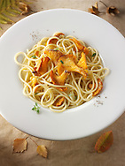 Wiild organic chanterelle or girolle Mushrooms (Cantharellus cibarius) or sauteed in butter and hebs with spaghetti