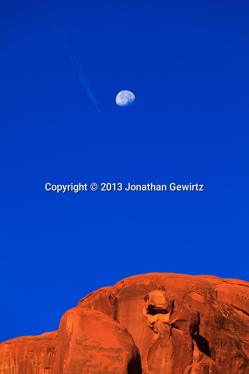 A distant jet aircraft appears to pass near the setting moon over rocky cliffs in Arches National Park, Utah. WATERMARKS WILL NOT APPEAR ON PRINTS OR LICENSED IMAGES.