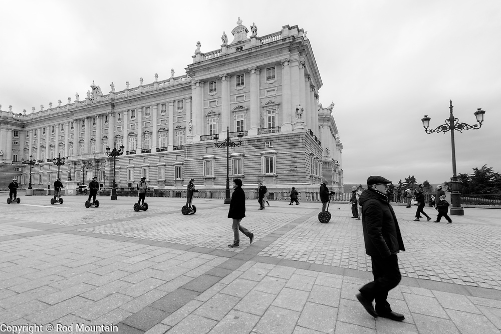 Madrid, Spain - February 15, 2018 - Tourists ride by on Segway transporters outside the Royal Palace in Madrid. <br /> <br /> Image: © Rod Mountain<br /> <br /> http://www.rodmountain.com <br /> <br /> Instagram<br /> @spain @visita_madrid<br /> <br /> FaceBook<br /> @spain.info @visitamadridoficial<br /> <br /> Twitter<br /> @spain @Visita_Madrid<br /> <br /> https://en.wikipedia.org/wiki/Royal_Palace_of_Madrid<br /> https://www.patrimonionacional.es<br /> https://www.esmadrid.com/en/tourist-information/royal-palace<br /> https://entradas.patrimonionacional.es/en-GB/informacion-recinto/6/palacio-real-de-madrid<br /> <br /> #streetfinder #streetmagazine #moodygrams#shotzdelight #1stinstinct #agameoftones#igersone#bwmasters #bwstyleoftheday #shotzdelight #hubs_united #jaw_dropping_shotz #photographyislife #worldshotz #main_vision #traveldreamy #worldcaptures #artofvisuals #instatravel #vacation #photostory #documentaryphoto #bnw_madrid #blackandwhiteisworththefight #bw_photooftheday#bw_crew #bnw_demand #monochromatic #tourismmadrid #spain🇪🇸