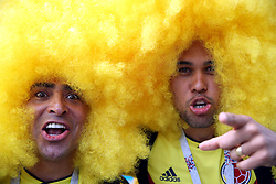 Two Colombia fans wearing giant yellow afro wigs in tribute to former player Carlos Valderrama before the FIFA World Cup 2018, Group A match at the Luzhniki Stadium, Moscow.