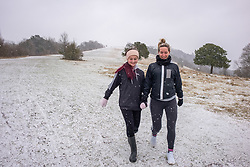 © Licensed to London News Pictures. 08/02/2021. Surrey, UK. Walkers Kelly Franky and daughter Brill enjoy the blizzard like snow conditions on top of Box Hill in Surrey this morning as Storm Darcy hits the South East with yet more snow and freezing temperatures today. The Met Office have issue numerous weather warnings for heavy snow and ice with disruption to travel, power cuts and possible stranded vehicles as the bad weather continues.  Photo credit: Alex Lentati/LNP