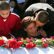 Santos Cisneros Alvarez kisses his mother, Senobia Alvarez, as she kneels next to the coffin of Lance Cpl. Julio C. Cisneros Alvarez, her son, with youngest child Marco Davila, 11, left, next to her during grave side services for the fallen Marine at Palm Valley Memorial Gardens in Pharr.<br /> Nathan Lambrecht/The Monitor