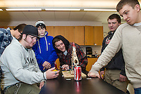 """Joanne Gilbert's CCR Applied Physics students try their hand at pin point precision using """"Robot Arms"""" Monday morning at Laconia High School.  Pictured:  Andrew West times River Richer as he drops a push pin into a Coca Cola can.  Watching (l-r) Tyler Reichel, Seth Noe, Dillon Ellsworth and Richard Humphreys .    (Karen Bobotas/for the Laconia Daily Sun)"""