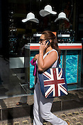 British consumer walks past a sunglasses shop featuring three hats suspended from the store window ceiling.