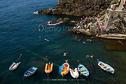 A view of swimmers in the harbor of Riomaggiore, Italy.