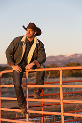 rugged cowboy sitting on a ranch fence at sunset