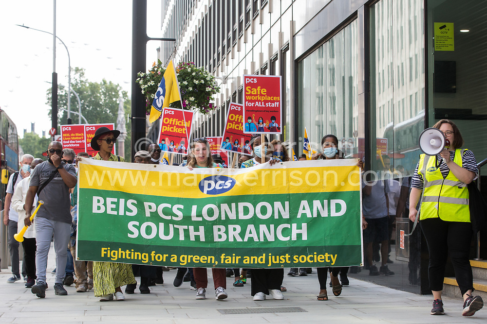 Members of the PCS trade union working for the outsourced contractor ISS march around their workplace at the Department for Business, Energy and Industrial Strategy (BEIS) on the second day of a 3-day strike on 20th July 2021 in London, United Kingdom. The striking cleaners, security guards and other support staff at the government department are demanding an end to low pay, improved working conditions, bonuses for having worked through lockdown, annual leave from last year and a Covid return-to-work protocol.