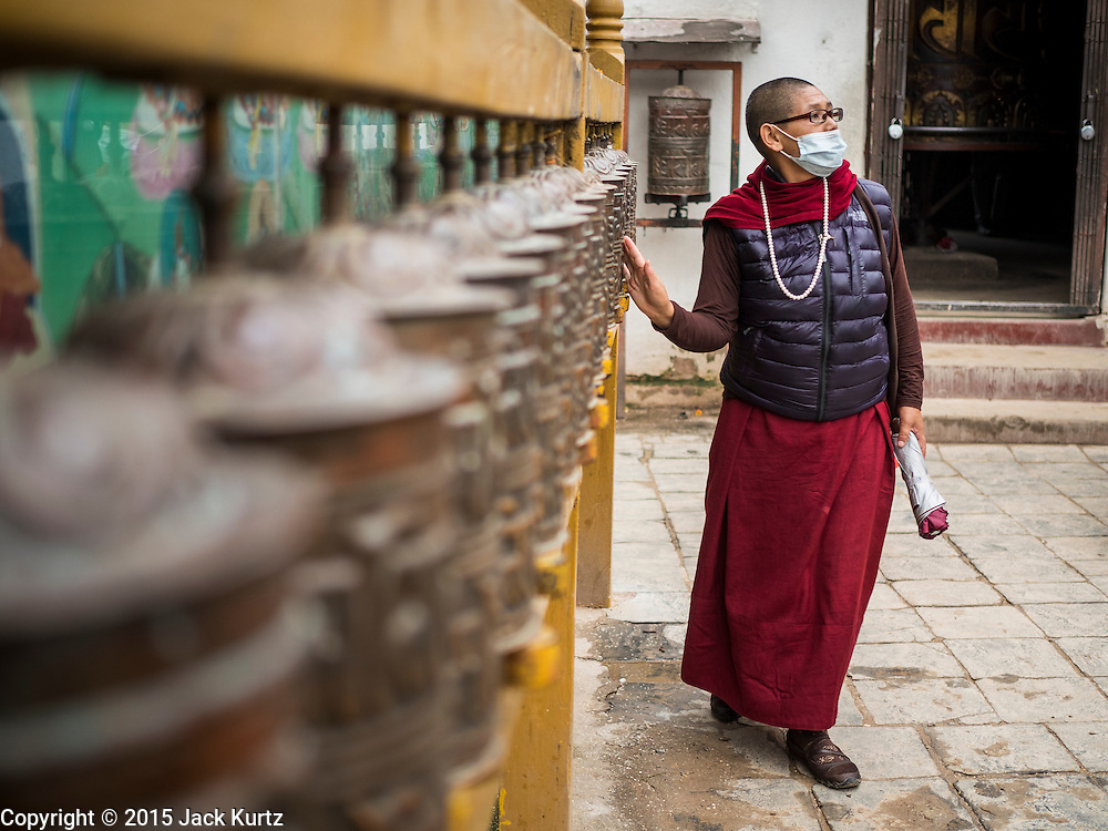 31 JULY 2015 - KATHMANDU, NEPAL:  A Tibetan Buddhist nun spins prayer wheels at Bodhnath Stupa. Bodhnath Stupa in the Bouda section of Kathmandu is one of the most revered and oldest Buddhist stupas in Nepal. The area has emerged as the center of the Tibetan refugee community in Kathmandu. On full moon nights thousands of Nepali and Tibetan Buddhists come to the stupa and participate in processions around the stupa. The stupa was heavily damaged in the earthquake of 25 April 2015 and people are no longer allowed to climb on the stupa, now they walk around the base and pray with butter lamps.  PHOTO BY JACK KURTZ